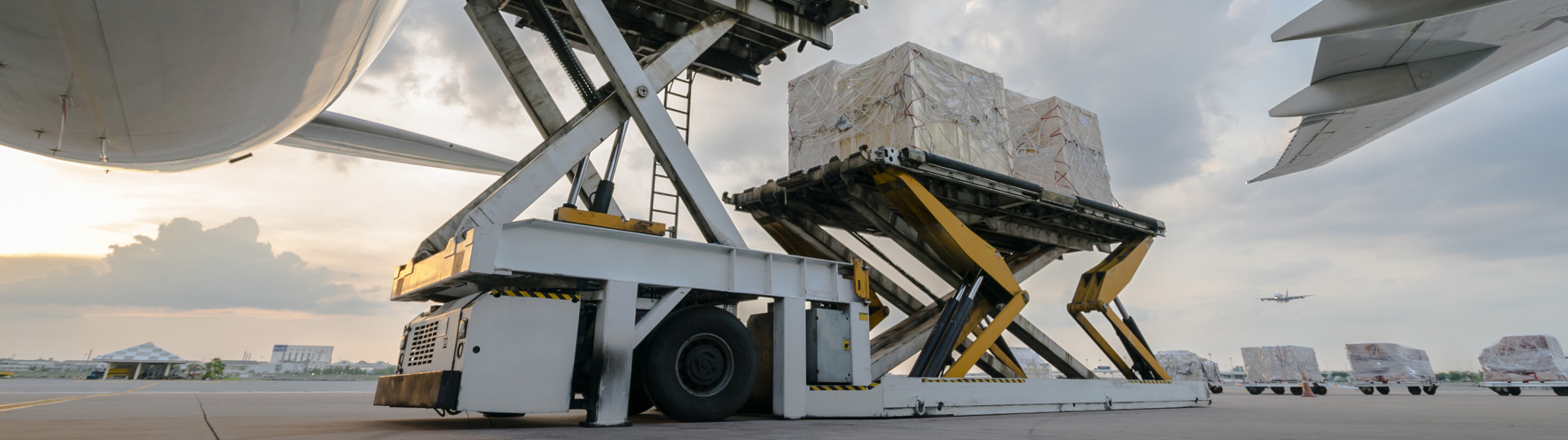 A cargo loader lifting up the cargo underneath an aircraft.